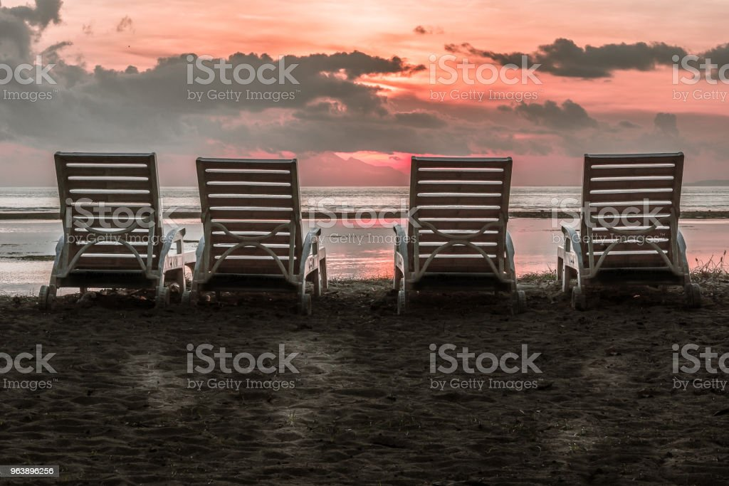 The backside of four sun loungers close to the beach in the tropical sunset - Royalty-free Bali Stock Photo