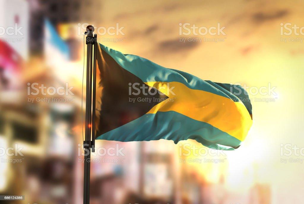 The Bahamas Flag Against City Blurred Background At Sunrise Backlight stock photo