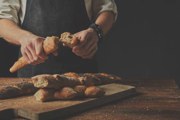 Der Bäcker hält die Baguette-Hälften in seinen Händen. – Foto
