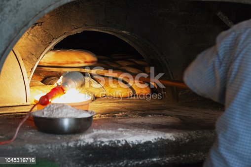 886308526 istock photo The baker takes out a loaf of bread from an old oven with a wooden shovel. 1045316716
