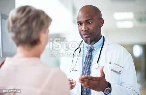 Cropped shot of a handsome mature male doctor talking to a female patient in the hospital corridor