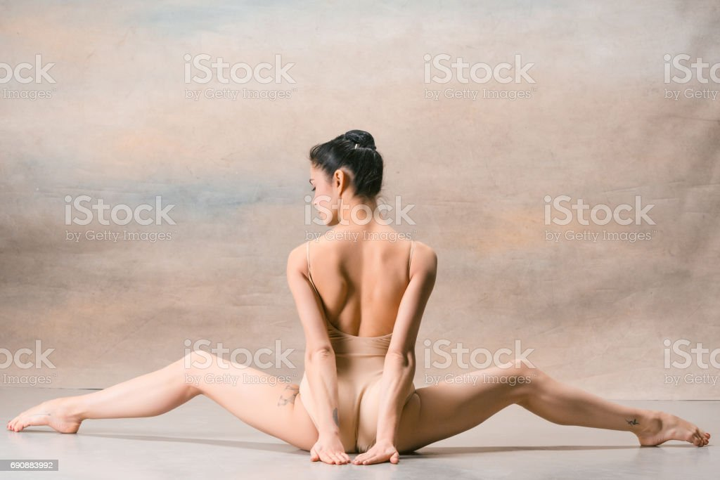 The ballerina is sitting with her back legs wide apart stock photo