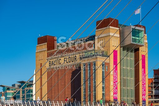 Newcastle, England - August 2, 2018: The Baltic Centre for Contemporary Art behind Gateshead Millennium Bridge on a beautiful summer afternoon.