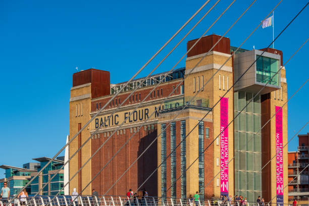 the baltic centre for contemporary art behind gateshead millennium bridge on a beautiful summer afternoon. - gateshead stock photos and pictures