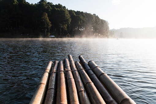 The bamboo raft floating on the reservoir with mist in the morning.