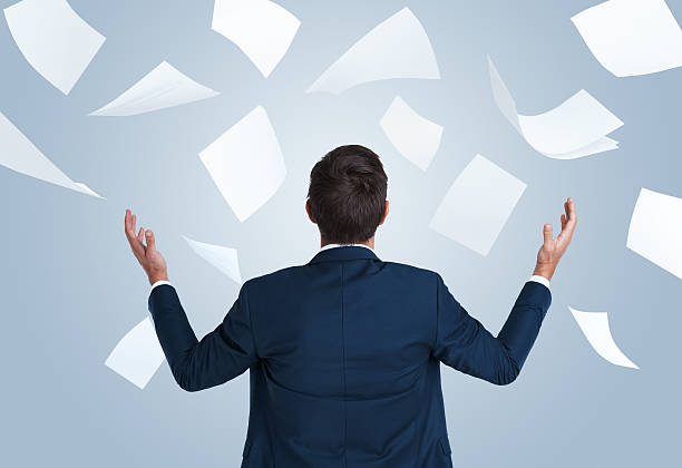 The bane of the businessman Rearview studio shot of a young businessman overwhelmed by paperwork surrounding stock pictures, royalty-free photos & images