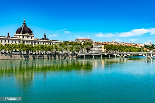 The banks of the Rhone at Lyon.  There are tourists walking over the bridge of pont Wilson at sunset with the Cathedral of Notre Dame de Fourviere in the background and Hotel Dieu behind the bridge.