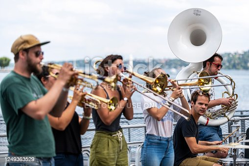 Geneva, Switzerland - August 24, 2018: The bare brass band busking at Geneva, Switzerland. Young boys and girls are earning money by using classic musical instruments (trombone, saxophone, oboe, drums) in street of Geneva. They are street musicians.