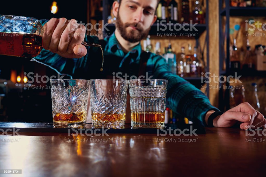 The barman pours alcohol into a glass. Close-up stock photo