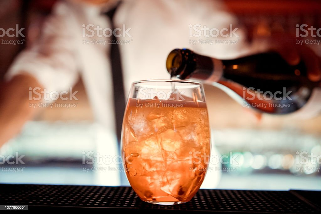 The barman pours Aperol into the cocktail close up stock photo