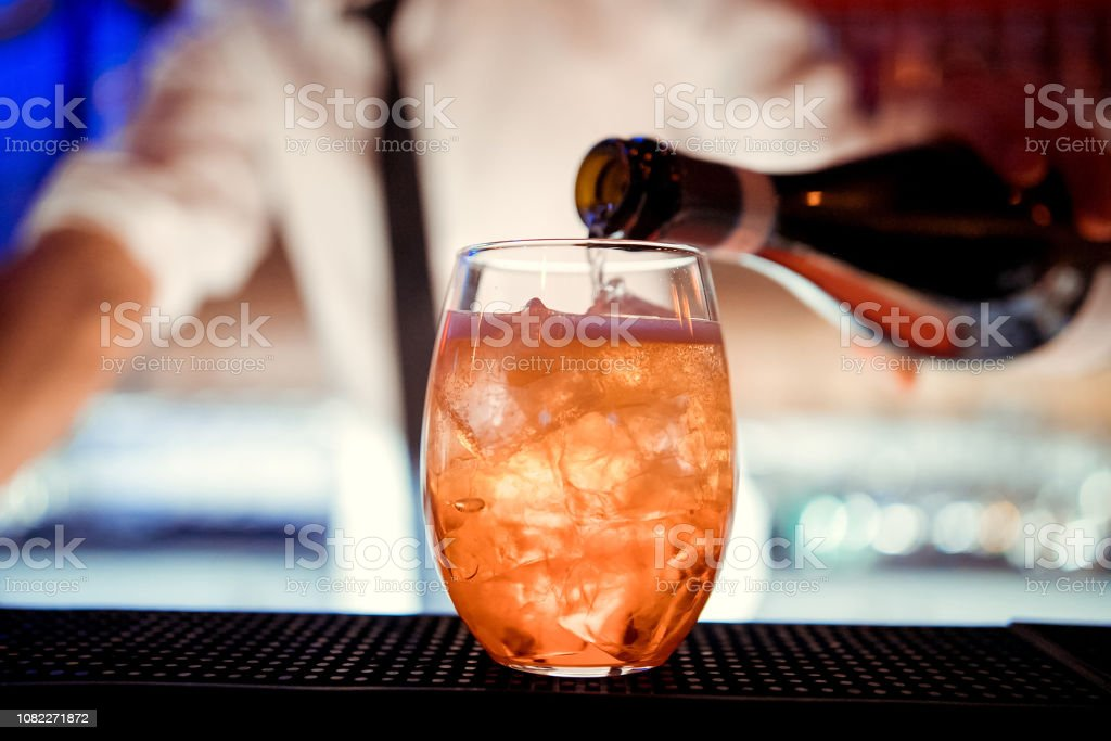 The barman pours Aperol into the cocktail of Aperol Spritz close up stock photo