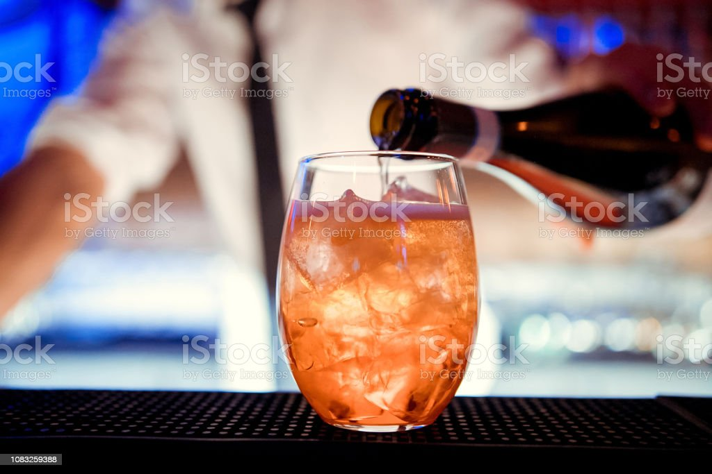 The barman pours champagne into the cocktail of Aperol Spritz close up stock photo
