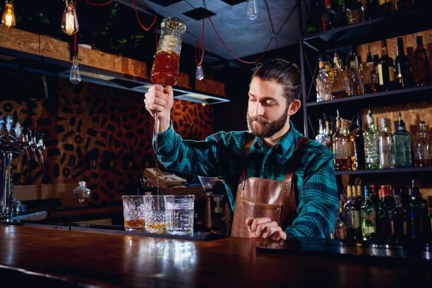 Le barman avec une barbe verse l'alcool dans les verres dans un bar. - Photo