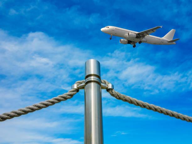 die barriere-zaun in form einer eisernen säule und seile des flughafens auf blauen himmelshintergrund. flugzeug landung. konzept - eisenstadt austria stock-fotos und bilder