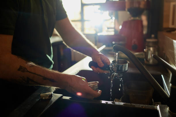 the bartender barista washing dishes  workplace. - commercial dishwasher stock photos and pictures