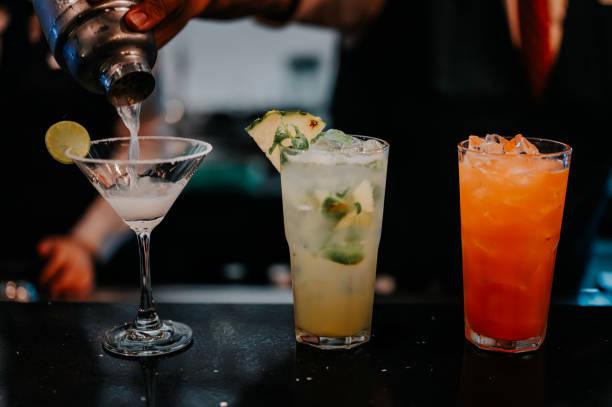 de barman maakt een cocktail aan de bar. - cocktail stockfoto's en -beelden