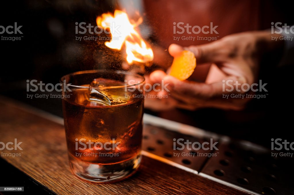 The bartender makes flame above cocktail close up stock photo
