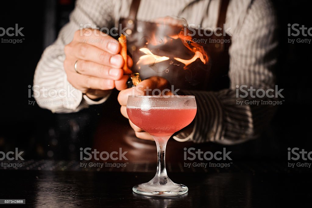 The bartender makes flame above cocktail stock photo