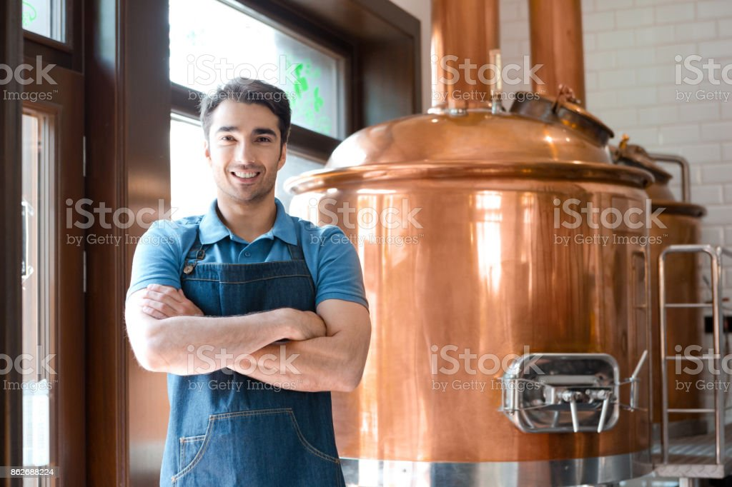 The bartender standing with crossed arms in microbrewery Happy bartender standing in front to copper vat and smiling at the camera. Adult Stock Photo