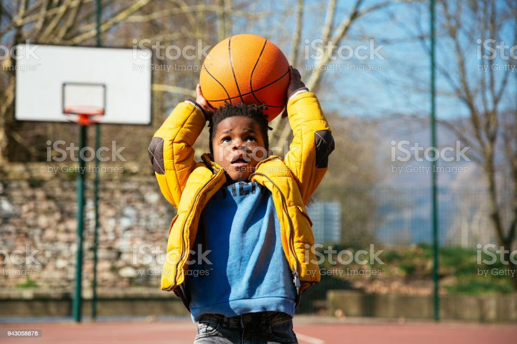 The basket is too high for little boys stock photo