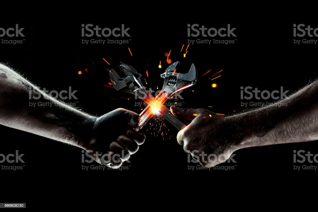 The battle of mechanics. Two wrenches cut sparks. stock photo