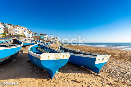 Atlantic Ocean and beach at Taghazout, a tourist area in Morocco that is receiving considerable investment in new hotels, apartments etc. In the foreground are fishing boats near the town itself.