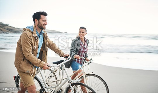 Shot of a couple walking on the beach with their bicycles