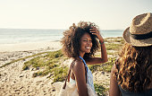 Shot of two young women spending time together at the beach