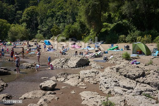 Lake Oswego, OR, USA - July 20, 2020: The Willamette River beach in a Lake Oswego city park is packed with visitors on a hot summer day amid the coronavirus pandemic.