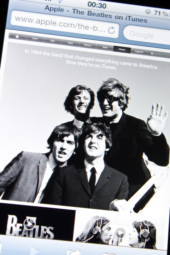 Istanbul, Turkey - May 27, 2011: Apple Iphone 4 screen showing the website of Apple Itunes homepage with the music band The Beatles. The website announces that the songs of The Beatles are now on sale on iTunes.