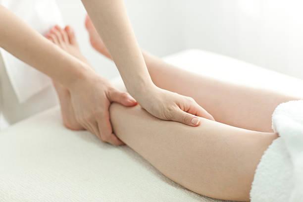 l'esthéticienne qui massages une jambe - mi jambe photos et images de collection