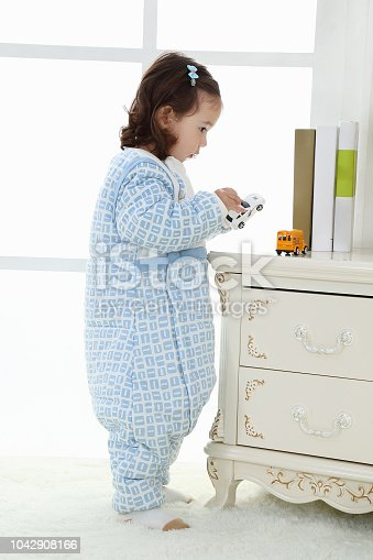 956002732 istock photo the beautife little girl in the pink bule pyjamas played in the room 1042908166