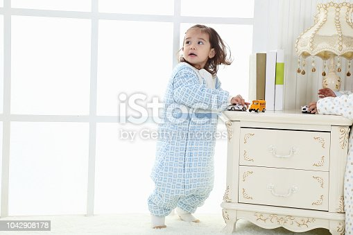 956002732 istock photo the beautife little girl in the pink bule pyjamas played in the room 1042908178