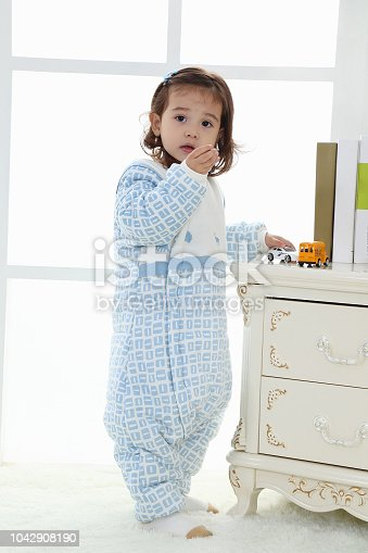 956002732 istock photo the beautife little girl in the pink bule pyjamas played in the room 1042908190