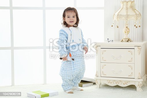 956002732 istock photo the beautife little girl in the pink bule pyjamas played in the room 1042908228