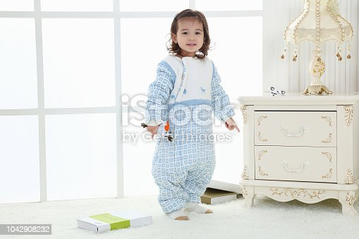 956002732 istock photo the beautife little girl in the pink bule pyjamas played in the room 1042908232