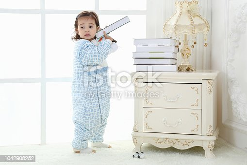 956002732 istock photo the beautife little girl in the pink bule pyjamas played in the room 1042908252