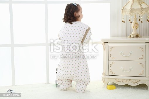 956002732 istock photo the beautife little girl in the pink bule pyjamas played in the room 1042908262