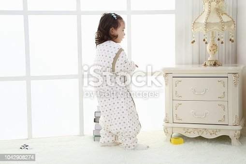 956002732 istock photo the beautife little girl in the pink bule pyjamas played in the room 1042908274