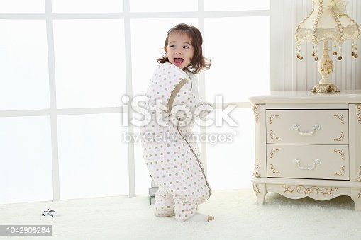 956002732 istock photo the beautife little girl in the pink bule pyjamas played in the room 1042908284
