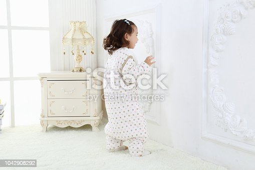 956002732 istock photo the beautife little girl in the pink bule pyjamas played in the room 1042908292