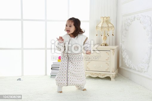 956002732 istock photo the beautife little girl in the pink bule pyjamas played in the room 1042908298