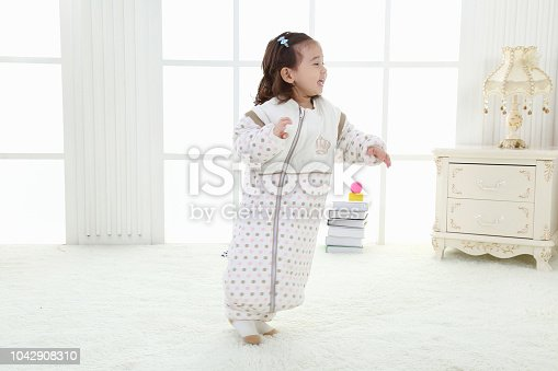 956002732 istock photo the beautife little girl in the pink bule pyjamas played in the room 1042908310