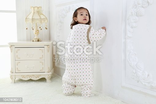 956002732 istock photo the beautife little girl in the pink bule pyjamas played in the room 1042908312
