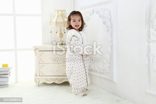 956002732 istock photo the beautife little girl in the pink bule pyjamas played in the room 1042908320