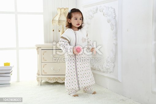 956002732 istock photo the beautife little girl in the pink bule pyjamas played in the room 1042908322
