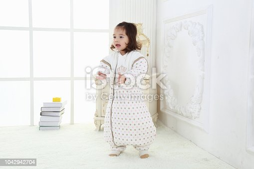 956002732 istock photo the beautife little girl in the pink bule pyjamas played in the room 1042942704