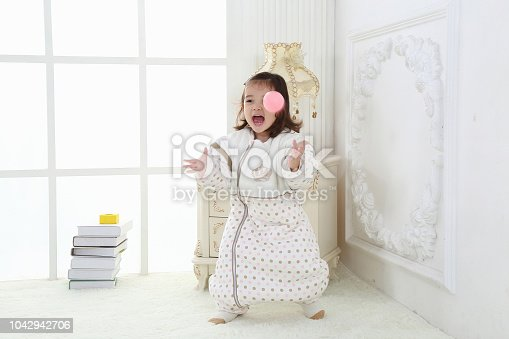 956002732 istock photo the beautife little girl in the pink bule pyjamas played in the room 1042942706