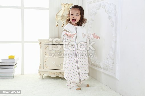956002732 istock photo the beautife little girl in the pink bule pyjamas played in the room 1042942714