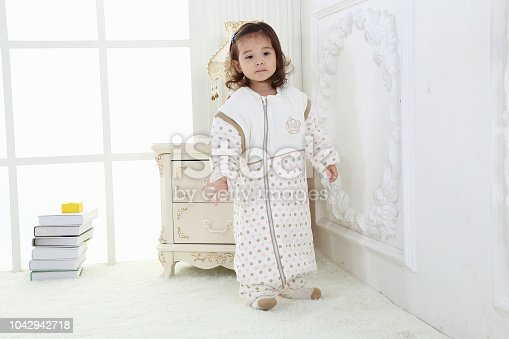 956002732 istock photo the beautife little girl in the pink bule pyjamas played in the room 1042942718